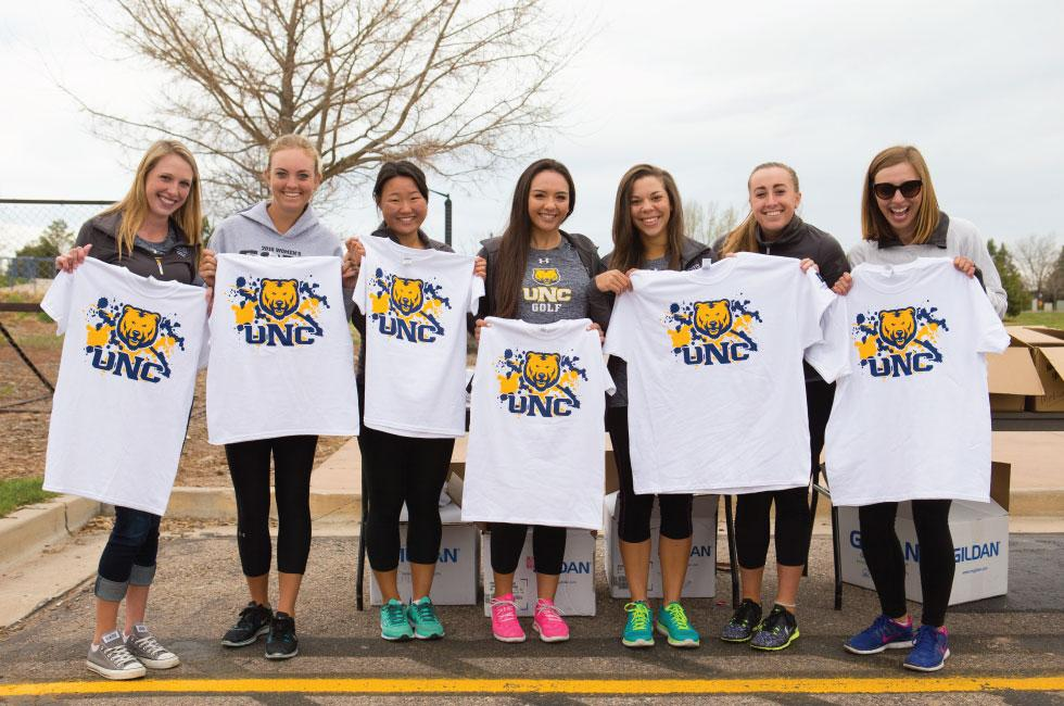 a team showing off their new women's walk shirts