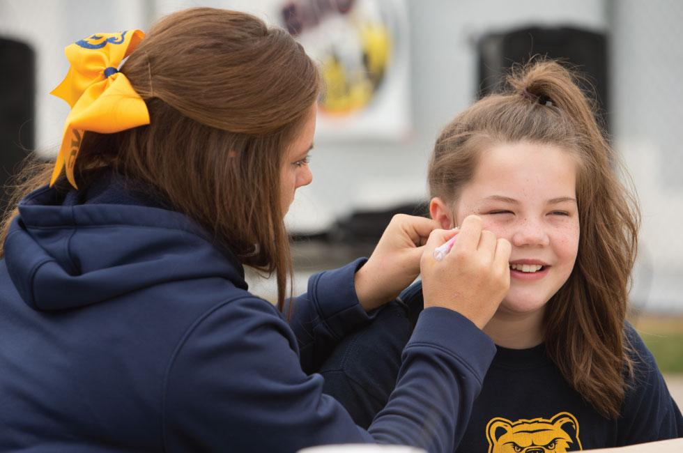 cheerleader painting a face at the women's walk