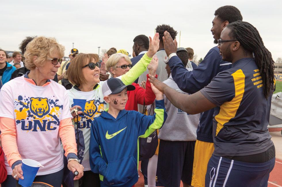 walkers get started and get high fives from student athletes
