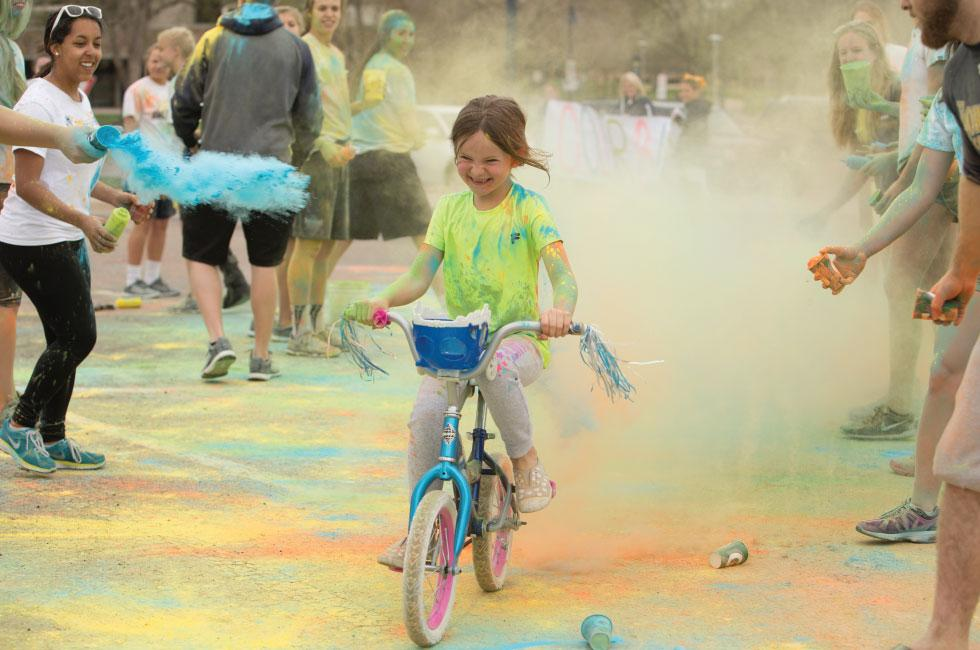 child riding her bike through a color cloud at the women's walk