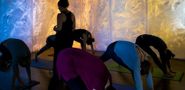 Mai-Fusco (closest to camera) joins  a yoga class surrounded by her art. Photos by Woody Myers