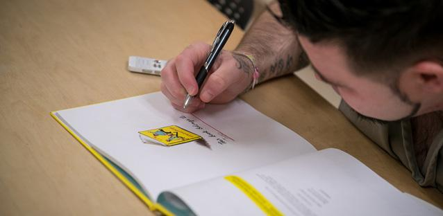 A Boulder County Jail inmate signs the children's book he recorded himself reading for his seven-year-old-son. Photo by Hunter Wilson