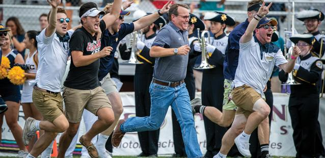 Andy joins students to bring out the football team during a home game. Photo by Brain Smith