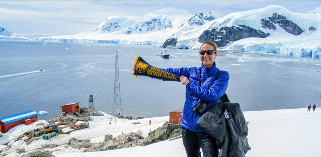 Cindy Shellito displays her UNC pride on a hill above a small Argentinian research station on Antarctica. The ship that carried Homeward Bound participants to Antarctica drifts in the background, waiting for participants to return from a shore excursion.