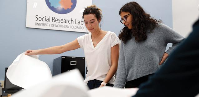 UNC Graduate students Caitie Graefe (left), of Greeley, and Hannah Conner, of Fort Collins, review the data and themes collected from President Andy Feinstein's strategic planning sessions in the Social Research Lab. Photo by Hunter Wilson