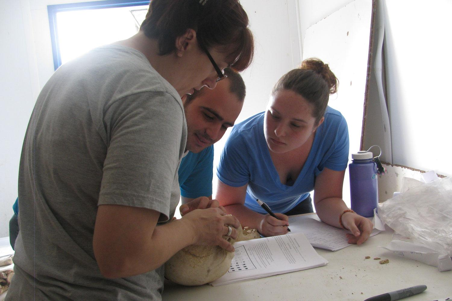 UNC students Jennifer Wright and Katelyn McEachern work with Albanian student Marlon to analyze skeletons in Albania.