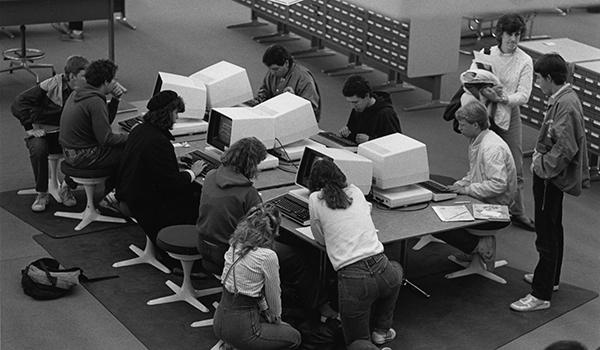 Students using the first computer catalog in the Michener Library reference area