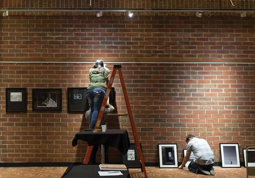 Art and Design students prepare their gallery displays on Friday night in the Two Rivers Lounge. Photo by Woody Myers