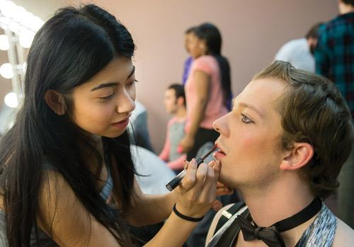 Theatre student Gabby Shaikh finishes stage makeup for fellow student and emcee Corbin George. Photo by Woody Myers