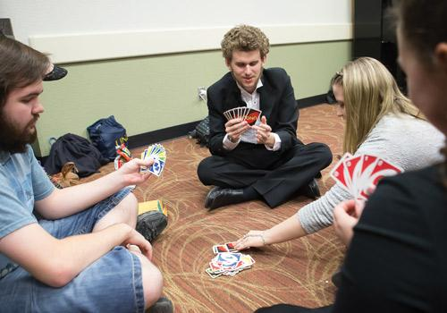 Students pass time until their performance by playing cards. Photo by Woody Myers