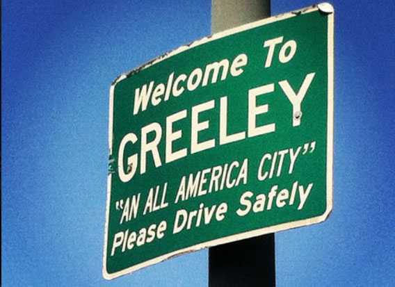 a green sign seen upon entering Greeley, Colorado