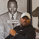 Rico Wint '08 sits in front of a photo of Martin Luther King Jr.