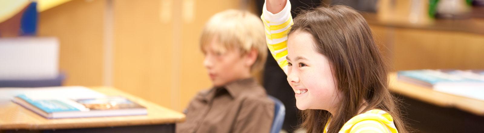 Child raising hand in classroom