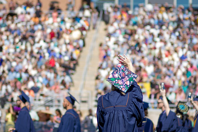 A student waves to families at UNC's commencement on Nottingham Field
