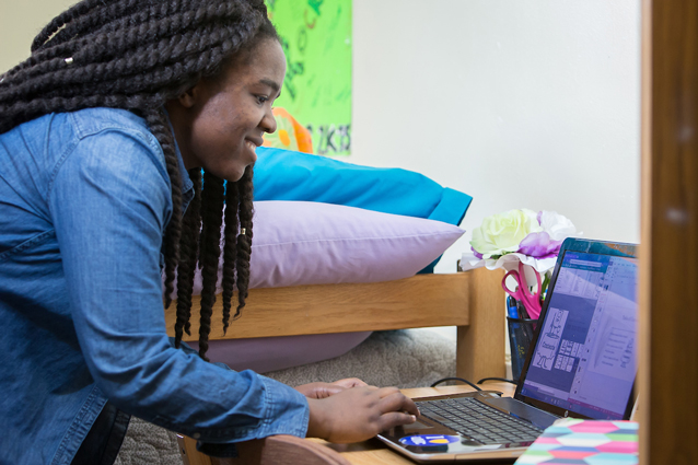 A young woman looks at her laptop and smiles