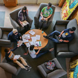 Students do homework and socialize in comfy chairs around a circular table