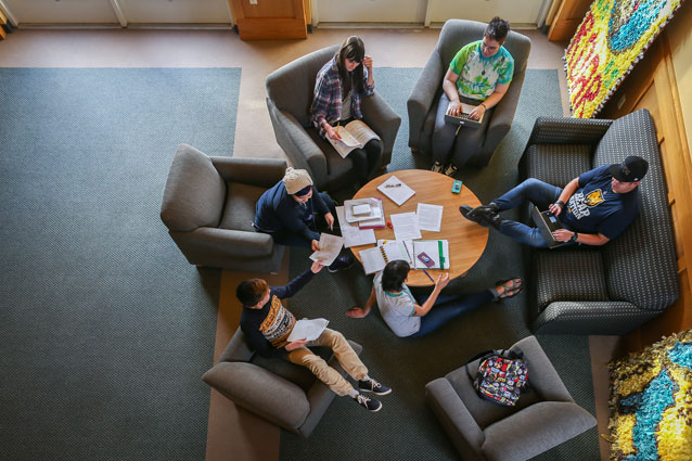 College students relax and do homework together gathered around a table