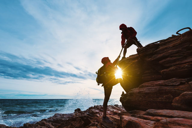 One hiker helping another up a cliff by the ocean