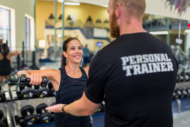 A woman lifting weights in the gym while her personal trainer advises her.