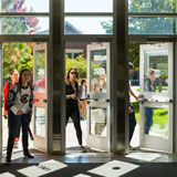 Students walk through three doors in a building on campus