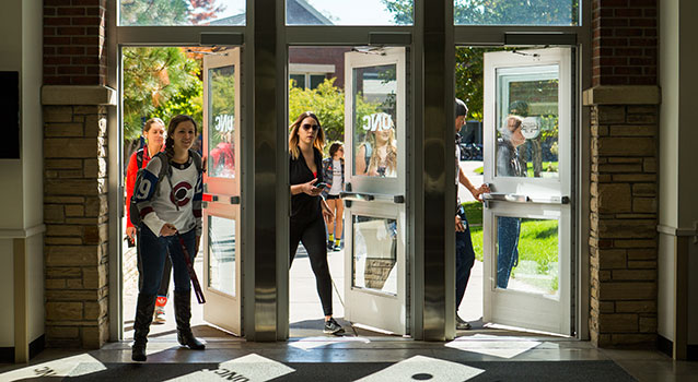 Students walk through three side-by-side glass doors on campus