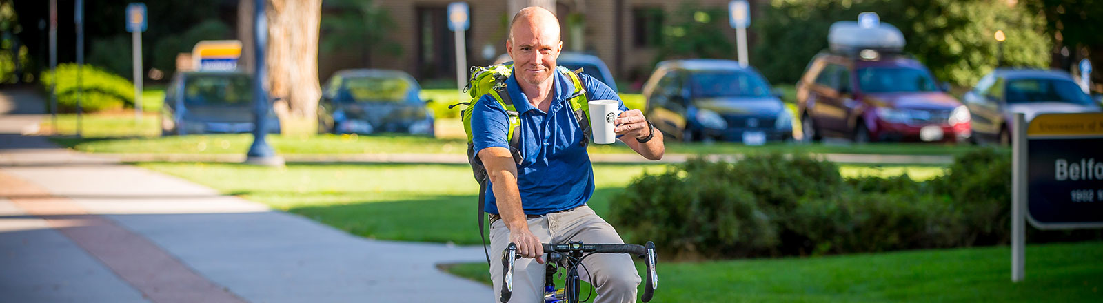 Staff member riding bicycle and drinking coffee