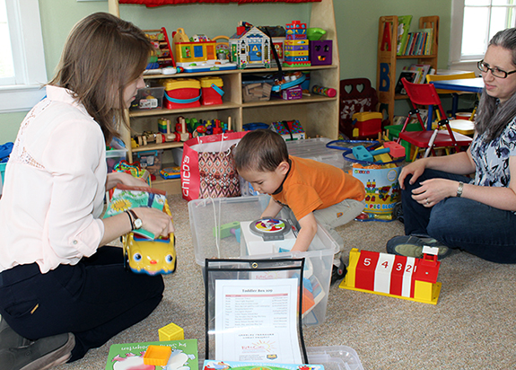 Child reaching into toy bin with two adults around.