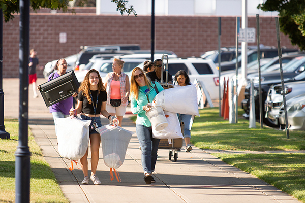 Students carrying loads of personal items during move in