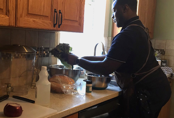 DeAndre Smith preparing a Garlic Shrimp Po Boy plate