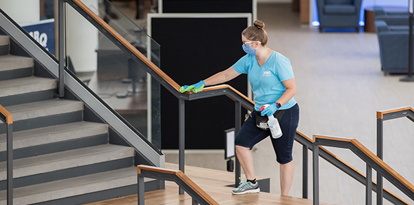 Custodial staff member cleaning handrail in campus commons