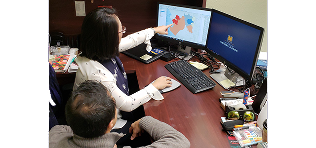 Drs. Lee and Ramirez reviewing a map of disease risk in Peru during El Nino.