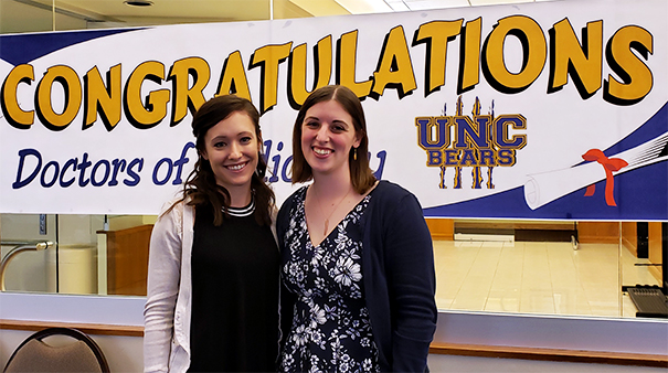 Jen Ruths and Ashley Stumpf pose after graduating with their Au.D.s