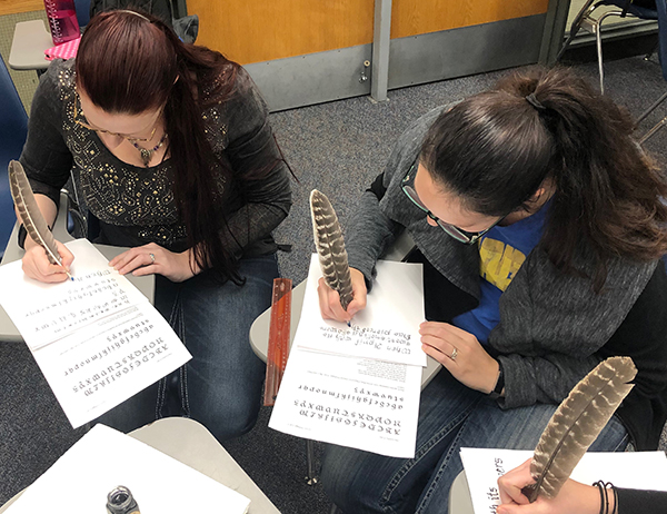 Other students using quills to write