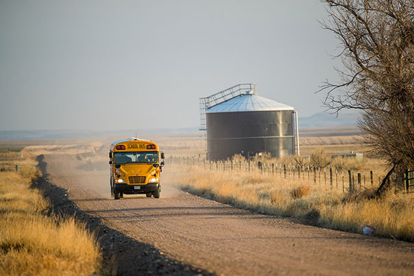 school bus driving on dirt road in rural Colorado
