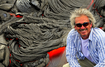 Steve Anderson poses in front of flowing lava.