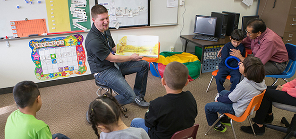 UNC student teacher reading to students in a classroom setting.