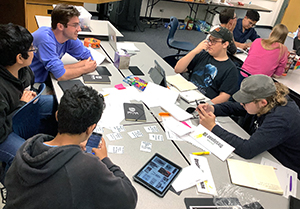 Sam Ptak, UNC Secondary Education Major, works with one of the design teams as they begin their prototype of an original game.