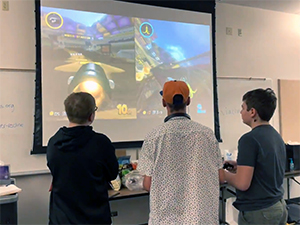 One of the design teams playtests MarioKart 8 in order to analyzes the game dynamics to build ideas for their team's game design.