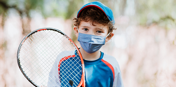 Child with racket and wearing mask