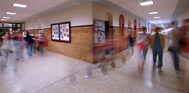 Timelapse photo of students walking around high school hallway