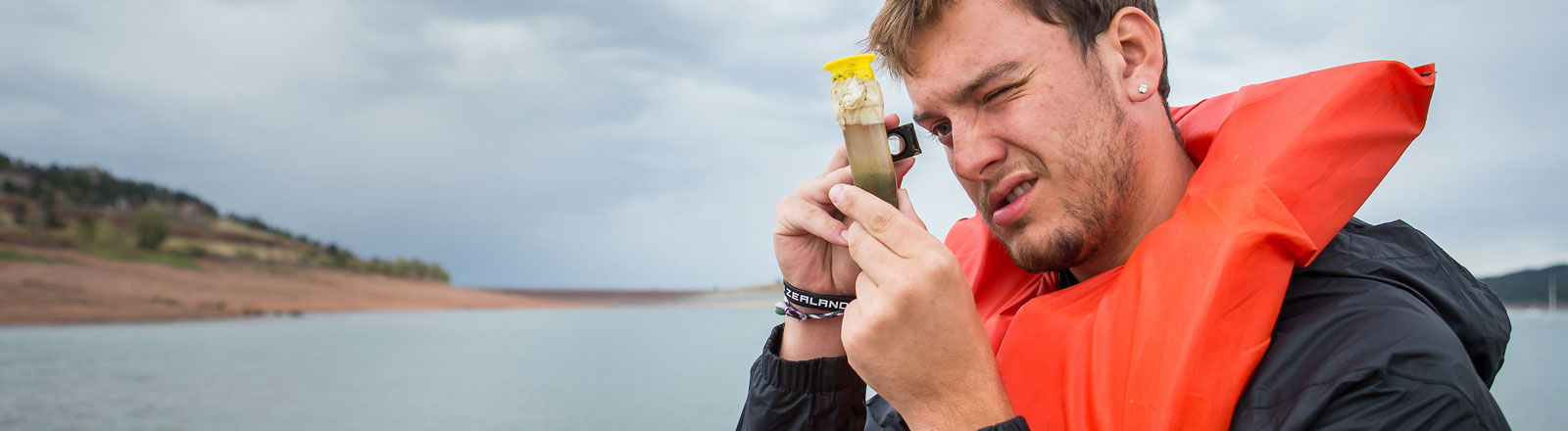 Student looking at a sample from Carter Lake during a fieldwork opportunity