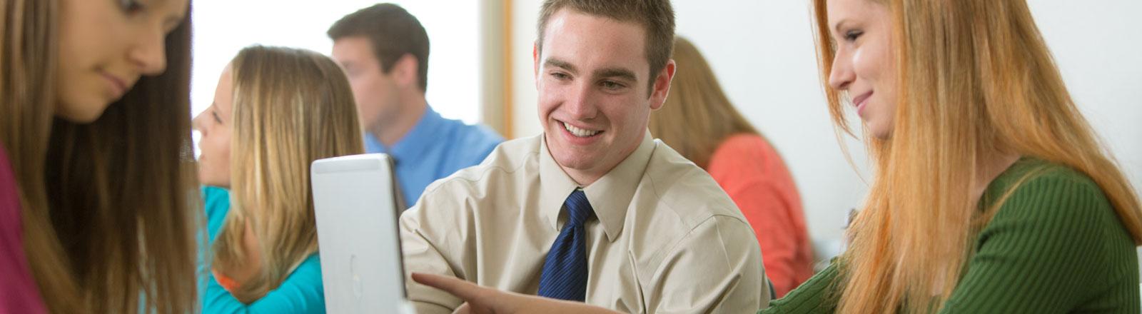 Students gathered looking at computer