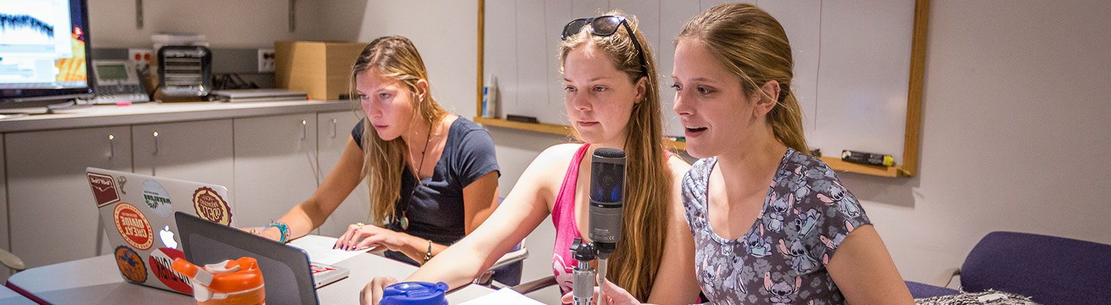 Group of students speaking into microphone in audiology clinic