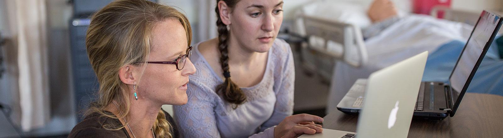 Student and professor observing computer screen