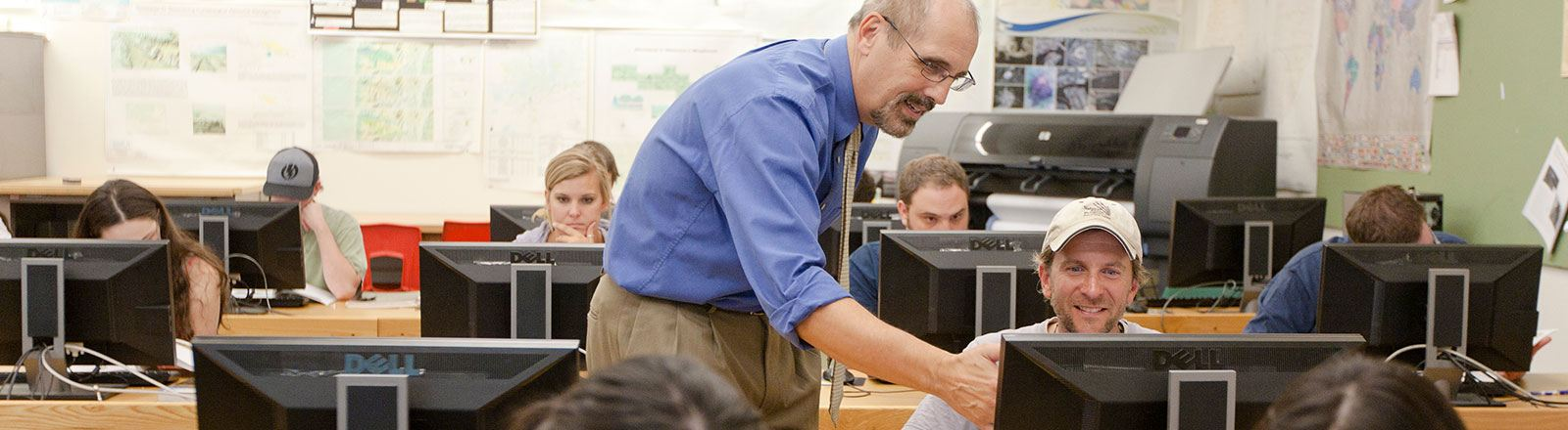 Geography professor and student working at computer