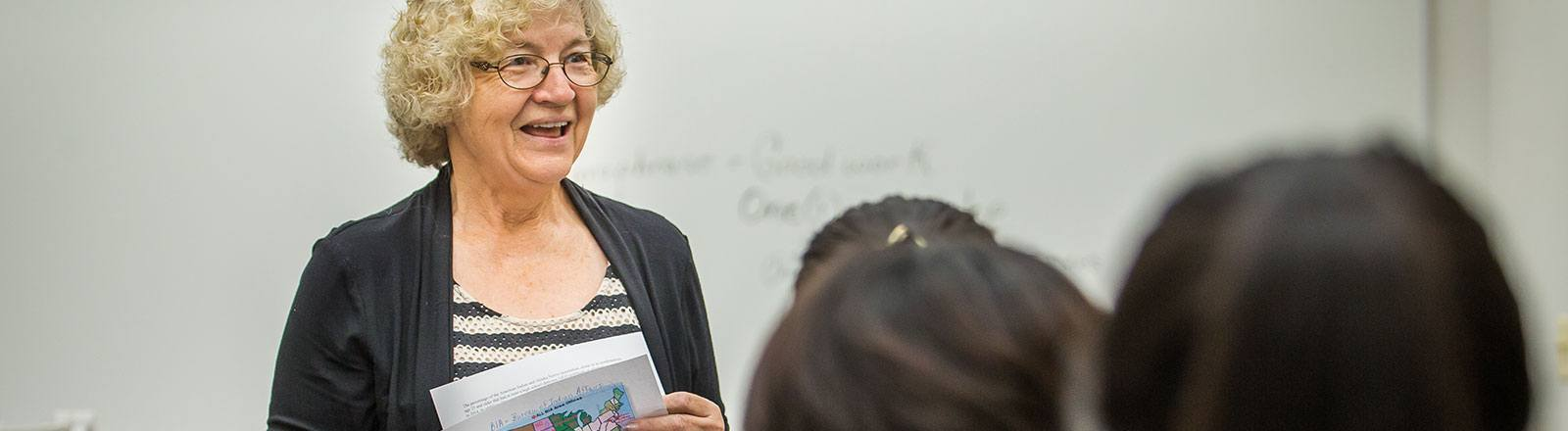 Professor in front of students speaking with paper of United States map