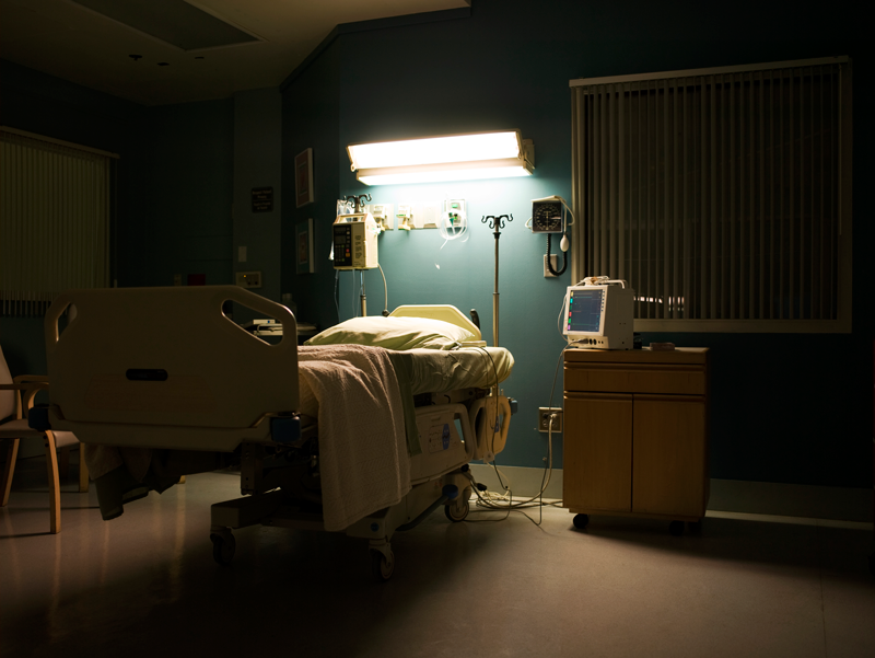 Darkened hospital room with light on over bed