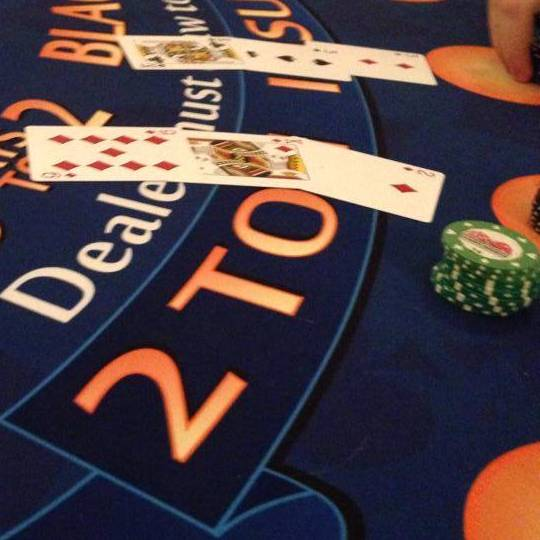 Card table displaying green poker chips and a two poker hands