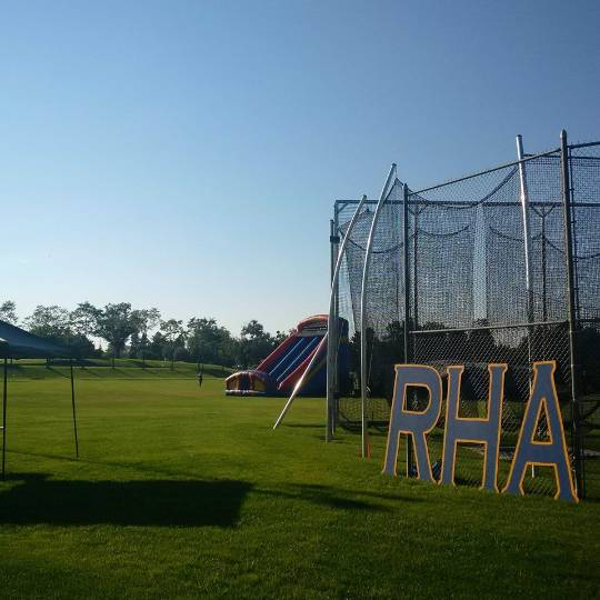 Blue RHA letters leaning agains a fence with an inflatable slide in the background