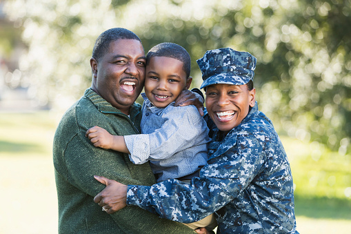 Family picture with male, child, and female in Navy uniform
